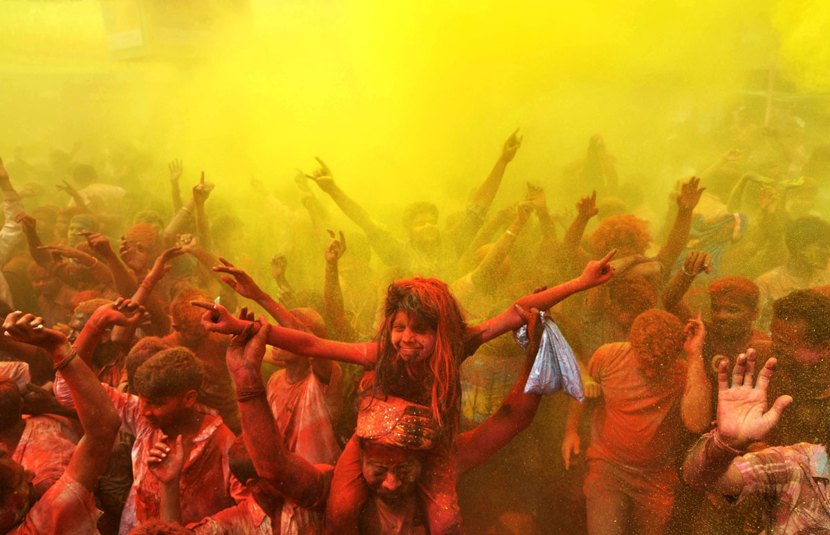 TOPSHOTS Indian revellers cover each other with coloured powder and dance while taking part in Holi festival celebrations in Guwahati on March 17, 2014. Holi, the Festival of Colours, is a popular Hindu spring festival observed in India and Nepal at the end of winter season on the last full moon day of the lunar month. AFP PHOTO / Biju BOROBIJU BORO/AFP/Getty Images ORG XMIT: