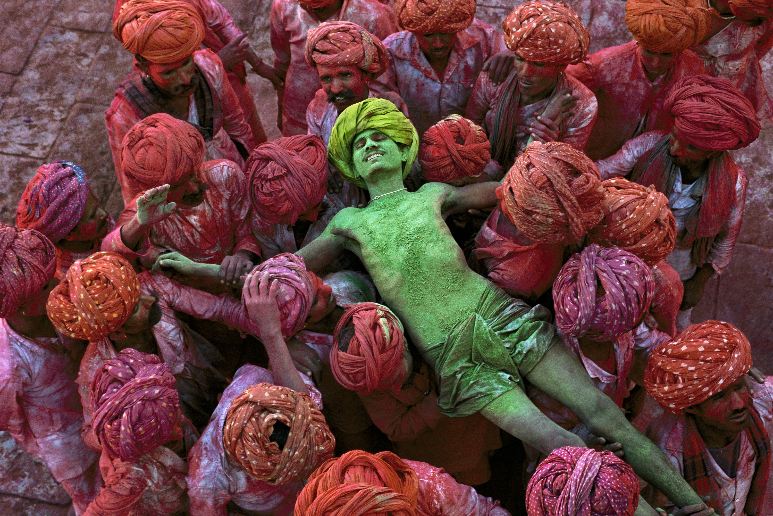 Holi festival, Rajasthan, India, 1996  The Holi festival is also known as the festival of colours and this image by McCurry shows why. With powder bombs exploding around him, this man is in a state of reverie as he is carried aloft through the crowd. In form and content it is an image of intense fervour and excitement.  Magnum Photos, NYC94205, MCS1996002K308  final print_MACRO'11   Phaidon  Iconic_Book